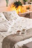 Настроение созданное лампой ночи стоя около кровати одело в зеленых растениях на белых белье и подушках картины в естественном ст стоковая фотография