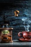 Насыщенная парами кофейная чашка и мельница на винтажной древесине стоковое изображение