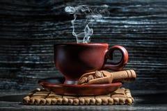 Насыщенная парами кофейная чашка и меньший деревянный ветроуловитель стоковое фото rf