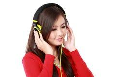 наслаждает детенышами нот девушки слушая довольно Стоковое Изображение RF