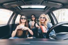 Наслаждаться их обедом в автомобиле 4 красивых молодых жизнерадостных женщины смотря один другого с улыбкой и есть принимают вне  Стоковые Изображения