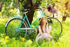 наслаждаться природой Горизонтальная съемка красивой молодой женщины держа глаза закрытый пока сидящ на траве с ретро велосипедом стоковое фото rf