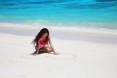 наслаждение Красивое беспечальное сердце чертежа девушки брюнет на san Стоковое Изображение