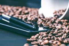 насладитесь Ручка грифеля на умном телефоне и сырцовой предпосылке кофе Энергия кофе фасолей сырцовый жать Естественная предпосыл Стоковые Фото