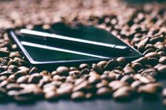 насладитесь Ручка грифеля на умном телефоне и сырцовой предпосылке кофе Энергия кофе фасолей сырцовый жать Естественная предпосыл Стоковые Изображения RF