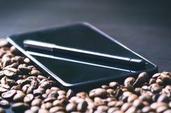 насладитесь Ручка грифеля на умном телефоне и сырцовой предпосылке кофе Энергия кофе фасолей сырцовый жать Естественная предпосыл Стоковые Изображения