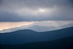 Наслоенные наклоны и облака горы в голубых тенях Стоковое Изображение