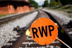 Натренируйте рельсы и оранжевый знак показывая путь стоковое изображение