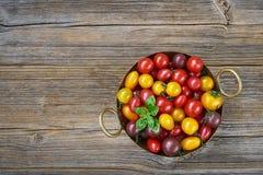 Натуральные продукты Красочные томаты вишни в деревенском дуршлаге на старом деревянном столе взгляд сверху, Стоковое фото RF
