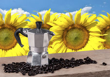 Натюрморт бака кофе на деревянном столе с предпосылкой солнцецвета Стоковая Фотография RF