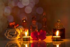 Натюрморт, бутылки ароматичных масел с свечами, цветками, полотенцем на лоснистой таблице Стоковые Изображения