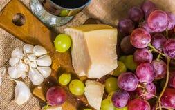 Натюрморт - взгляд сверху желтой и красной виноградины муската, сыра, чеснока и бокала вина на деревянной доске и холсте Стоковые Фото