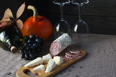 Натюрморт виноградин, тыквы, бутылки, стекел, сыра и сосиски на таблице Стоковые Фото