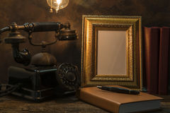 Натюрморт винтажного телефона с картинной рамкой и дневником дальше Стоковые Изображения RF