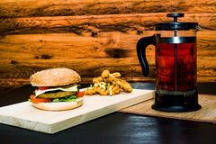 Натюрморт - гамбургер с прессой француза чая стоковые изображения