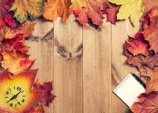 Натюрморт кленовых листов, часов, блокнота и ручки стоковое изображение