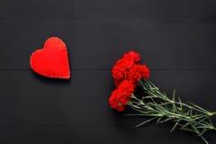 Натюрморт красных гвоздик и handmade сердца Стоковые Изображения