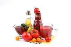 Натюрморт красных и желтых томатов, бутылки томатного соуса и оливкового масла на белой предпосылке Стоковые Изображения