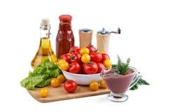 Натюрморт красных и желтых томатов, бутылки томатного соуса и оливкового масла на белой предпосылке Стоковая Фотография RF