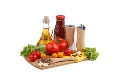 Натюрморт красных и желтых томатов, бутылки томатного соуса и оливкового масла на белой предпосылке Стоковые Фото