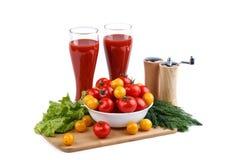 Натюрморт красных и желтых томатов и 2 чашек сока томата на белой предпосылке Стоковые Фото