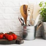 Натюрморт кухни на белой предпосылке кирпичной стены: различные разделочные доски, инструменты, зеленые цвета для варить, свежие  Стоковое Изображение RF