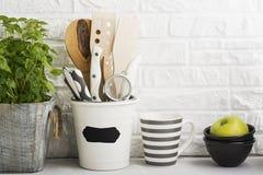 Натюрморт кухни на белой предпосылке кирпичной стены: различные разделочные доски, инструменты, зеленые цвета для варить, свежие  Стоковое Фото