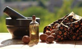 Натюрморт миномета, разбросанных гаек и бутылки масла против запачканной зеленой предпосылки Стоковые Изображения