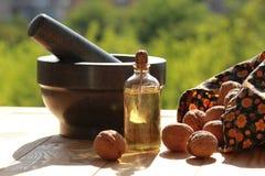 Натюрморт миномета, разбросанных гаек и бутылки масла против запачканной зеленой предпосылки Стоковая Фотография RF
