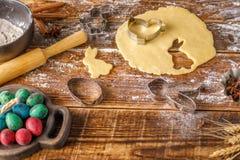Натюрморт на деревянной предпосылке Тесто для печениь и вычисляемых прессформ на ем Стоковое Фото