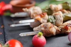 Натюрморт на черной предпосылке Сочные kebabs от свинины на протыкальниках Мясо сваренное на открытом огне и свежих овощах Стоковые Фото