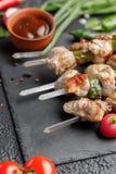Натюрморт на черной предпосылке Сочные kebabs от свинины на протыкальниках Мясо сваренное на овощах открытого огня свежих и соусе стоковое фото