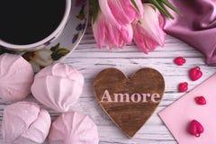 Натюрморт дня ` s валентинки элегантный с тюльпаном цветет чашка знака формы сердца zephyr зефиров coffe красного на белом деревя Стоковая Фотография