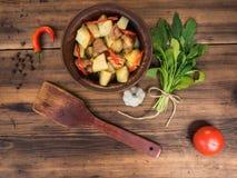 Натюрморт овощей, испеченных картошек с мясом, овощей, чеснока, перца на предпосылке деревянного стола сельско Стоковые Фото
