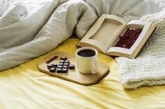 Натюрморт осени весны Завтрак в кровати Белая спальня домашняя помадка Книги, цветки, шоколад и кофейная чашка Плоское положение Стоковое фото RF
