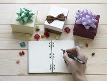 Натюрморт рождества с подарочными коробками и сочинительством руки в тетради тетради стоковая фотография