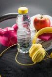 Натюрморт розового поднятия тяжестей, наушников, полотенца и яблока Стоковые Фото