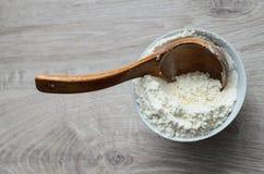Натюрморт сельской кухни Белая мука в шаре фарфора с деревянной ложкой handmade на деревянной предпосылке Стоковое Изображение RF