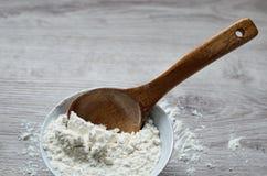 Натюрморт сельской кухни Белая мука в шаре фарфора с деревянной ложкой handmade на деревянной предпосылке Стоковое Фото