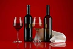Натюрморт со стеклами вина на красной, лоснистой предпосылке стоковые изображения rf