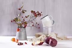 Натюрморт с боярышником, чашкой чаю и чайником на белой деревянной предпосылке Стоковое фото RF
