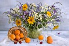 Натюрморт с букетом, вишнями и абрикосами лета Стоковое Фото