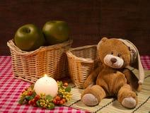 Натюрморт с медведем, свечой и яблоками Стоковые Изображения RF