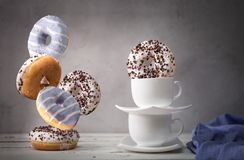 Натюрморт с падая donuts и белыми чашками Стоковое фото RF