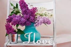 Натюрморт с сиренью цветет в бирюзе вазы помещенной на деревянной предпосылке Стоковое Изображение RF