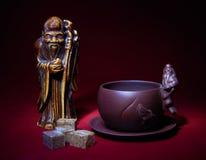 Натюрморт с статуэткой бога чая, чашки и шишек o Стоковые Фотографии RF