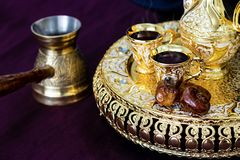 Натюрморт с традиционным золотым арабским комплектом кофе с dallah, jezva бака кофе, чашкой и датами Темная предпосылка Стоковое фото RF