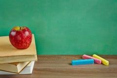 Натюрморт с учебниками и яблоком против классн классного стоковые фотографии rf