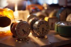 Натюрморт, часы час-сигнала тревоги на таблице Много различных сигналов тревоги, малая глубина поля Стоковое Изображение RF