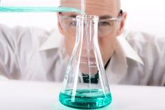 Наука Гай заполняя склянку Erlenmeyer с жидкостью Teal стоковое изображение rf